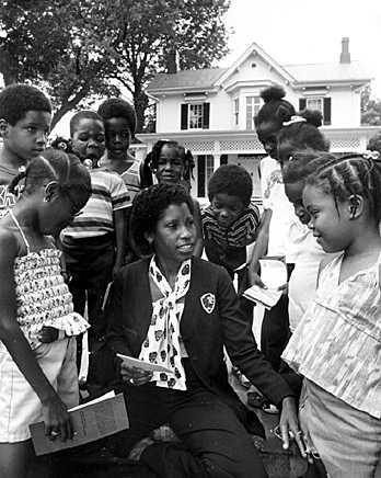 Black woman park ranger. Sitting in front of Frederick Douglass' house. The house is white in the background. The house has a huge tree next to it. The children are looking at the Black woman park ranger with interest.