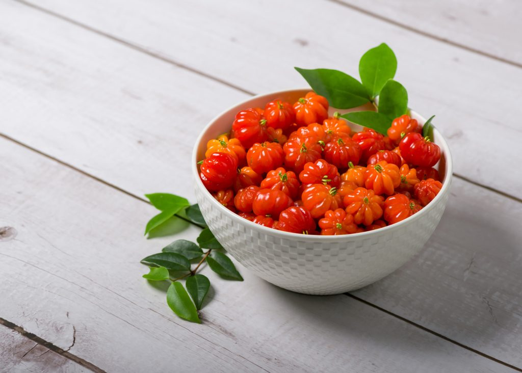 Surinam cherry in a white bowl on a wooden table.