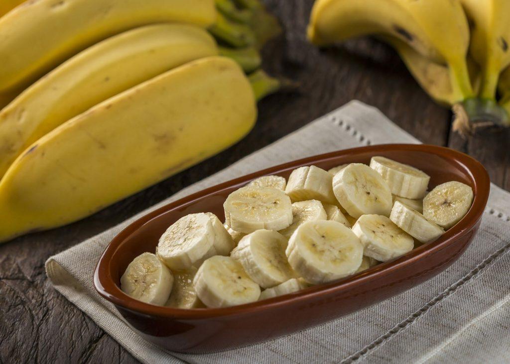 Bunch of bananas with sliced bananas on the table