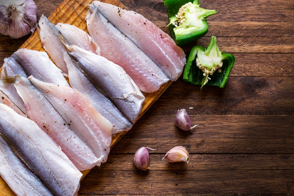 Raw fish on top of a wooden background, table top flat lay