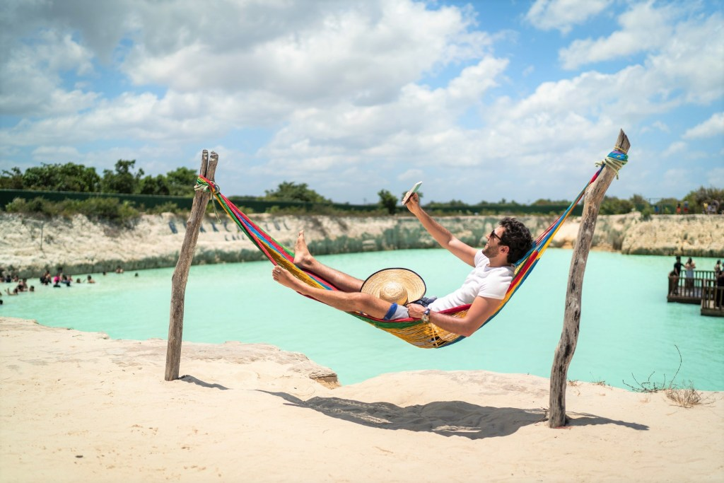 Man in a hammock taking a selfie / doing a video call using smartphone at the beach in Jericoacoara