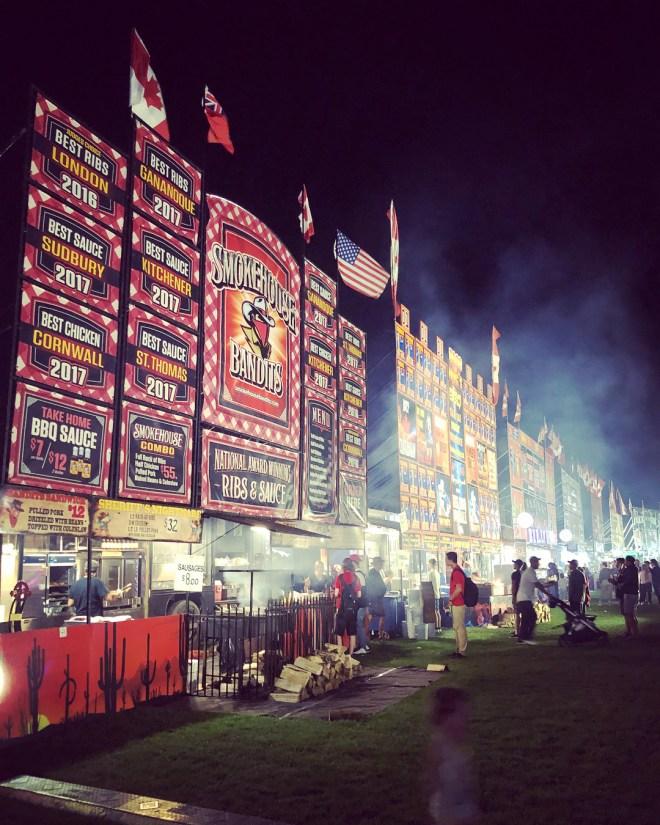 Row of smokehouse vendors lighting up Riverside park at night during Guelph Ribfest. Photo by @jessmass__ on Instagram