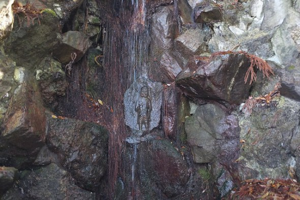 A Buddhist carving behind the trickling Fudo Falls