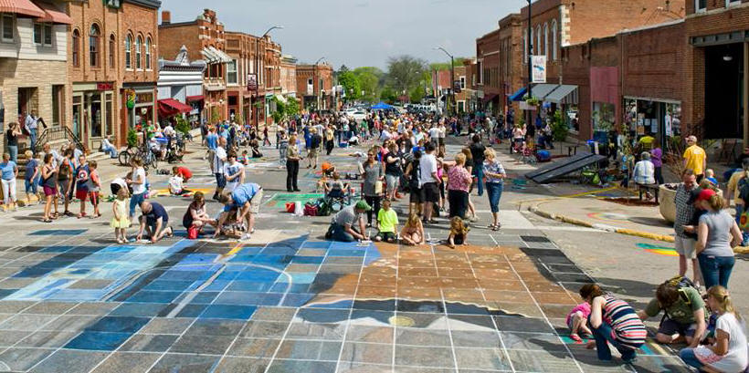 "Chalk the Walk 2015 photo of the street and participants working on the collaborative piece of art, Grant Wood's ""American Gothic"""