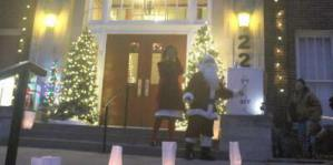 Photo of Santa and Mrs. Claus turn on holiday lights on First Street Community Center building.