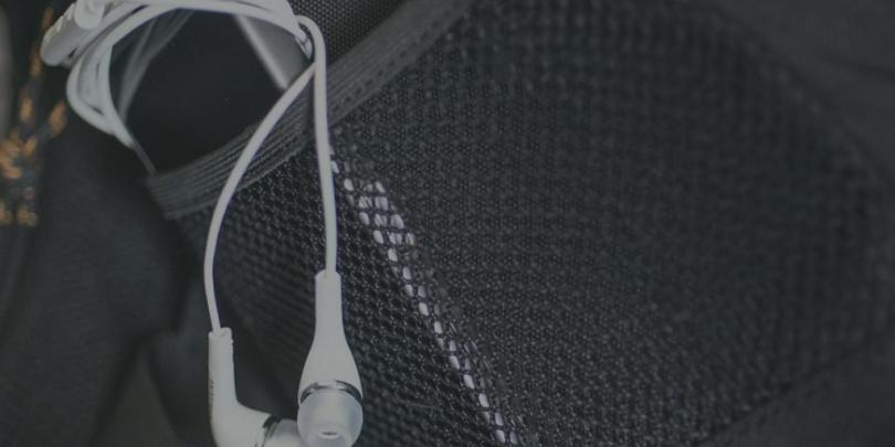 Phone with headphones in pocket of bag