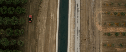 Goliath Season 3: Hello trouble, come on in. Billy McBride drives his red mustang into town. Aerial shot.