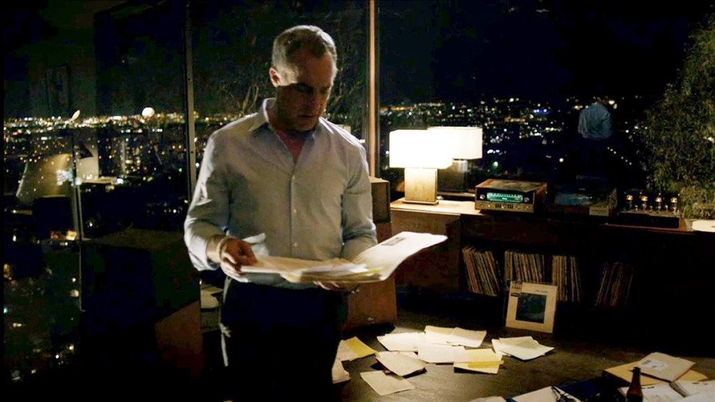 Bosch in his hilltop apartment with a record player in the background