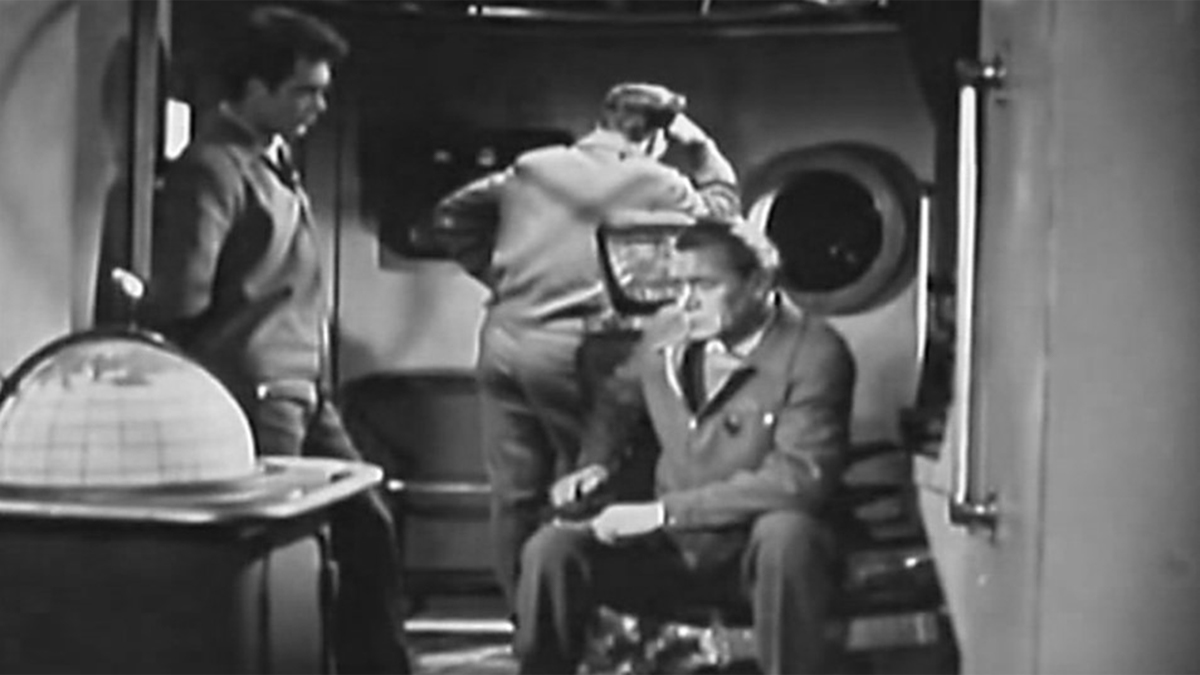Scene inside spaceship to three pensive astronauts in film Voyage to the Prehistoric Planet (1965) aka Planeta Bur (1965) aka Planet of Storms (1965)