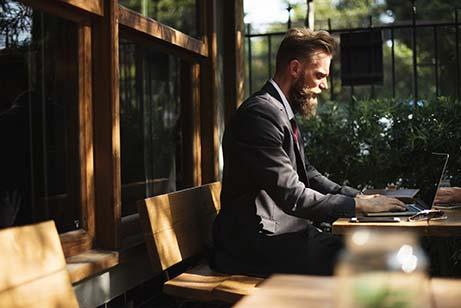 Man about beard on laptop working outside