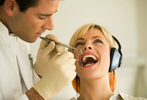 getty_rm_photo_of_woman_wearing_headphones_at_dentist