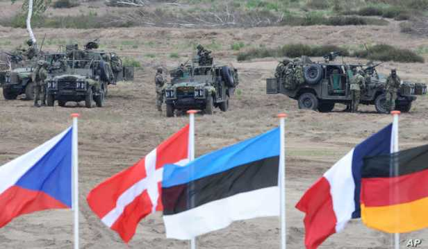FILE - Flags wave in front of soldiers who take positions with their army vehicles during the NATO exercises near Swietoszow Zagan, Poland, June 18, 2015.