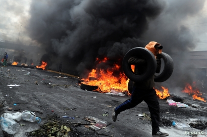 A demonstrator holds tires as he runs during a protest against Ecuador's President Lenin Moreno's austerity measures in Quito,…