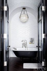 This clean and handsome globe is perfectly placed above the tub and finishes off the room. I love the heavy brass chain detail around the globe with the subway tiles and antique tub.