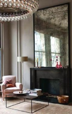 The crystal, teardrop 1960s chandelier is perfect in this clean, pastel pink sittingroom. The contemporary take on an antique mirror above the mantle is a great compliment to the simple but elegant piece.