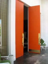These bold orange lacquered doors create quite the entrance at the Perkerin Palm Springs. We also love orange with brass and avocado!
