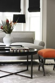 A pop of orange in this chic dove grey neutral room does the trick perfectly