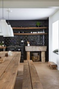 This masculine kitchen embodies rustic, casual design. Using black subway tiles against the stark white walls with natural elements of stone and reclaimed wood furniture allow are the perfect balance of function and design