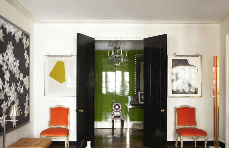 Todd Romano chose these bold orange chairs to flank the entrance from the lacquered avocado green foyer to a clean white drawing room.