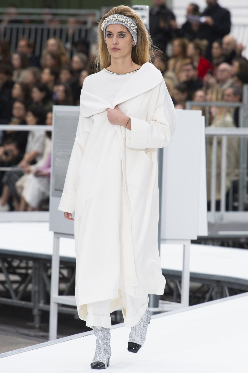 model wearing white coat walks down runway at chanel show