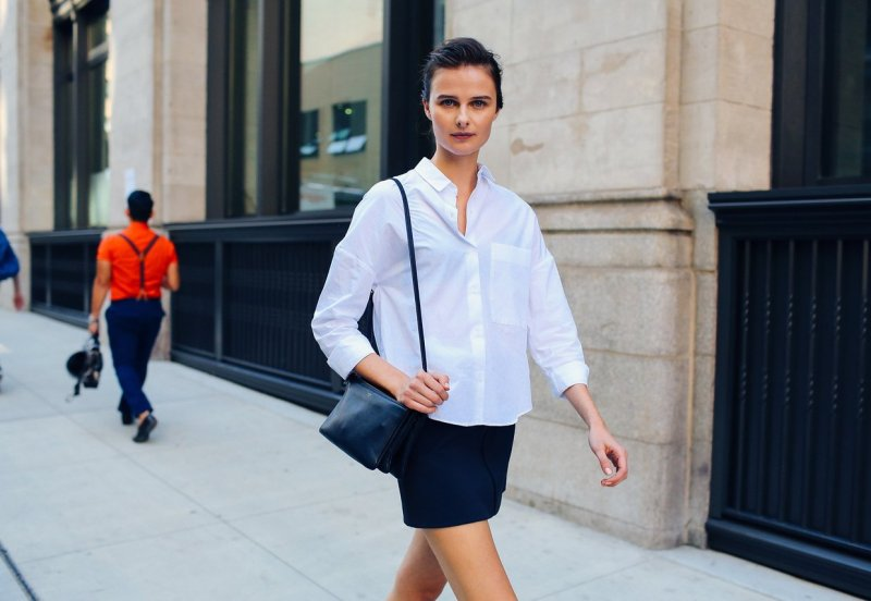 Girl seen in a classic style type street style outfit. Wearing a white button up, skirt and celine crossbody