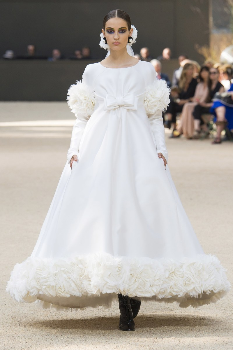 Model walking down runway at Chanel fall 2017 couture show in white ball gown wedding dress