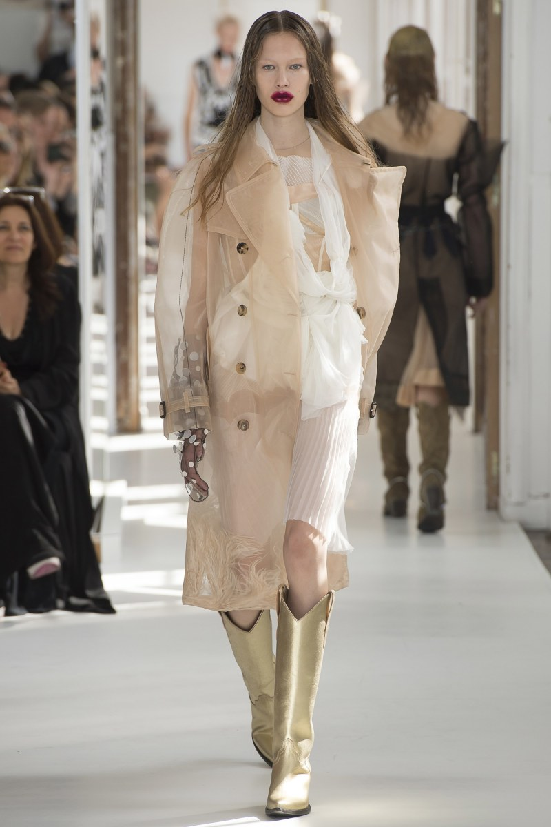 Model walking down the runway at margiela fall 2017 couture show in a sheer trench coat and boots