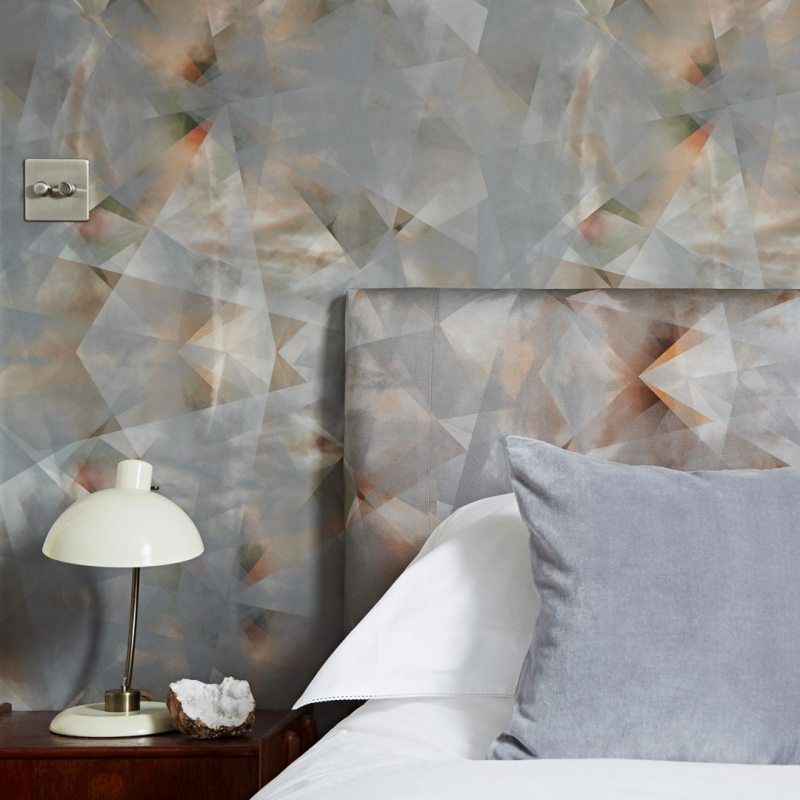 geometric gray and burnt wallpaper with a matching headboard and white bedspread and lamp