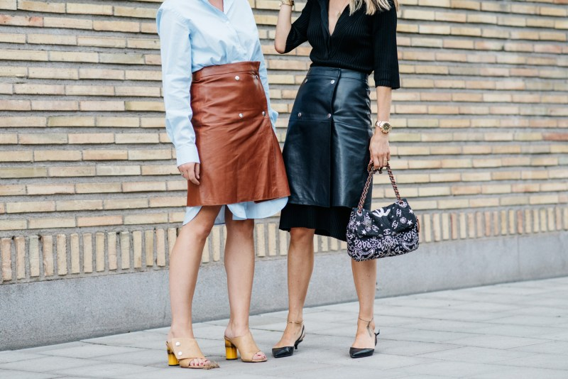 Two women wearing skirts layered over button down work dresses