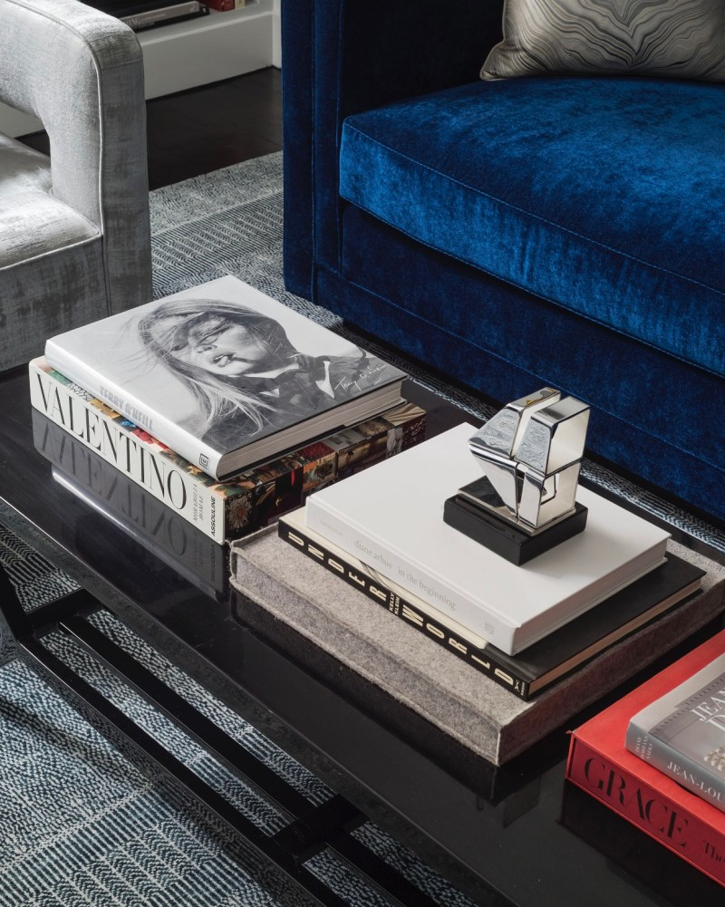 nyc apartment furnished with blue velvet sofa, coffee table furnished with books