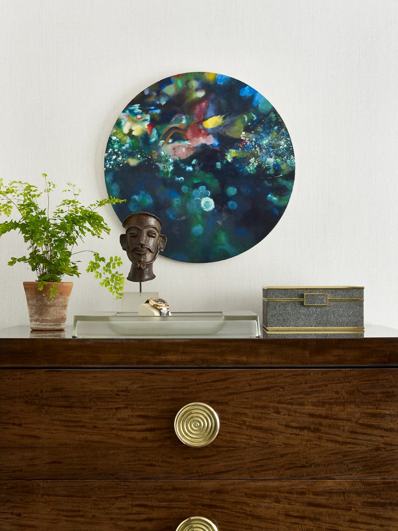 Image of interiors magazine spread featuring Joe Lupo VT Home. Image is a detail shot of a vintage walnut dresser with objects styled on it and a circle colorful art piece hanging above.