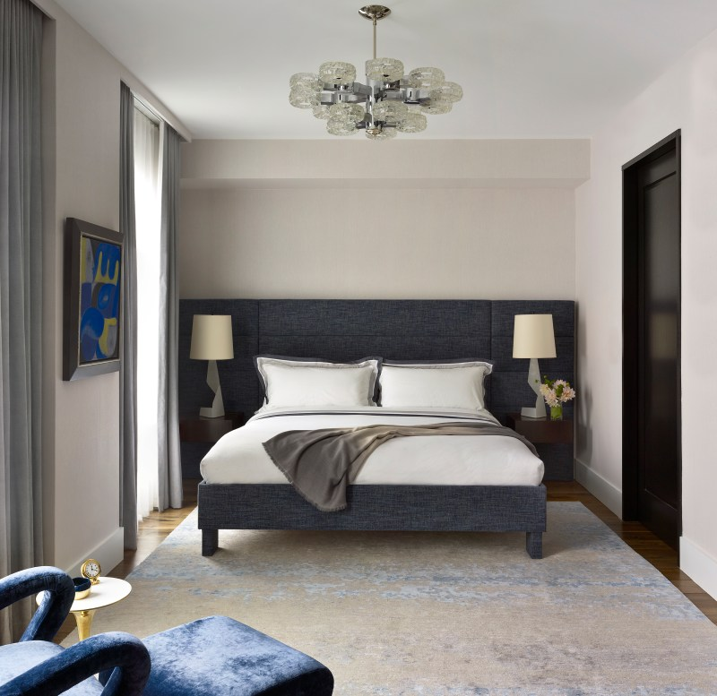 Image of interiors magazine spread featuring Joe Lupo VT Home. Image features a bedroom in a chelsea loft with an upholstered blue bed with headboard and floating side tables with lamps, chandelier from John Salibello, blue and gold carpet by stark, blue and yellow art on the wall and blue chair.