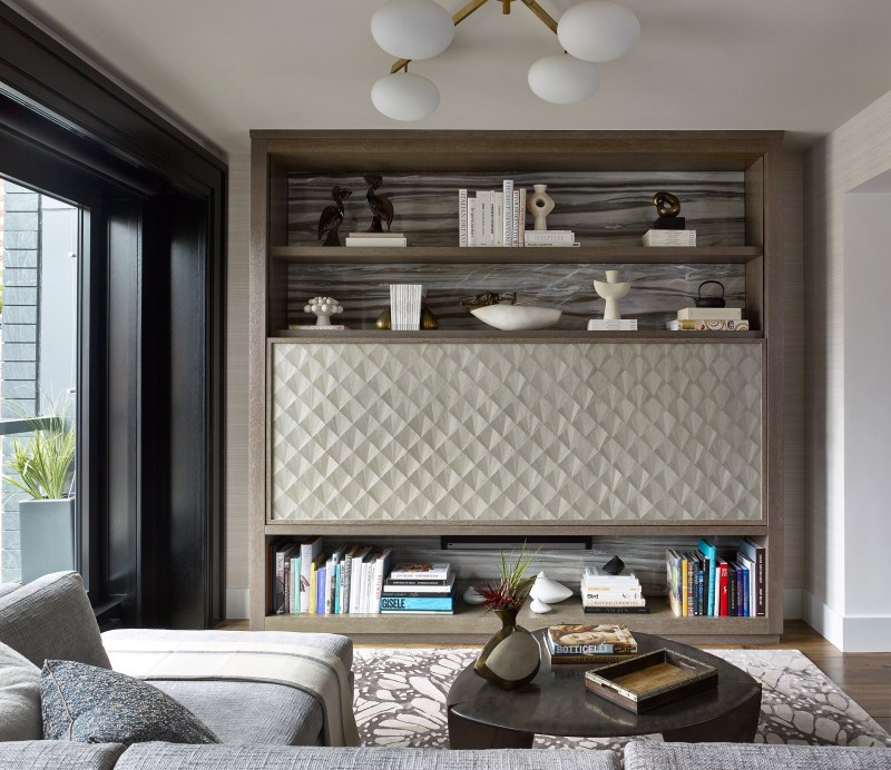 Photo of a living room in chelsea designed by Joe Lupo, founder of VT Home, featuring a wall unit with a remote controlled TV panel, white japanese ceramics, books, blanc de chine, rosenthal porcelain, maya romanoff wood veneer, monarch alexander mcqueen print silk carpet by the rug company, sonos unit, bronze guitar pick custom table, murano glass seagulls, a beige cashmere throw, mid century Arredoluce 5 arm brass chandelier with frosted white globes,