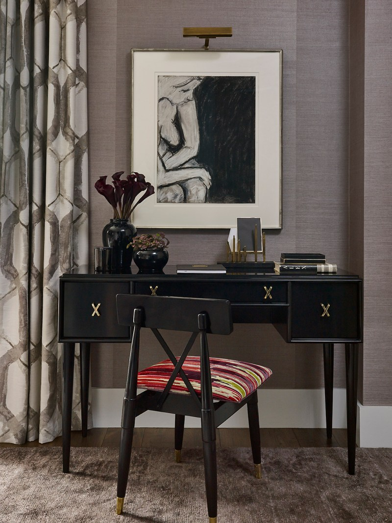 Image of interiors magazine spread featuring Joe Lupo VT Home. Image features an office with ethnic print curtains by romo, purple silk rug by stark carpet, antique chair with colorful fabric by pierre frey, black antique desk, various objects styled on desk and art work above desk.
