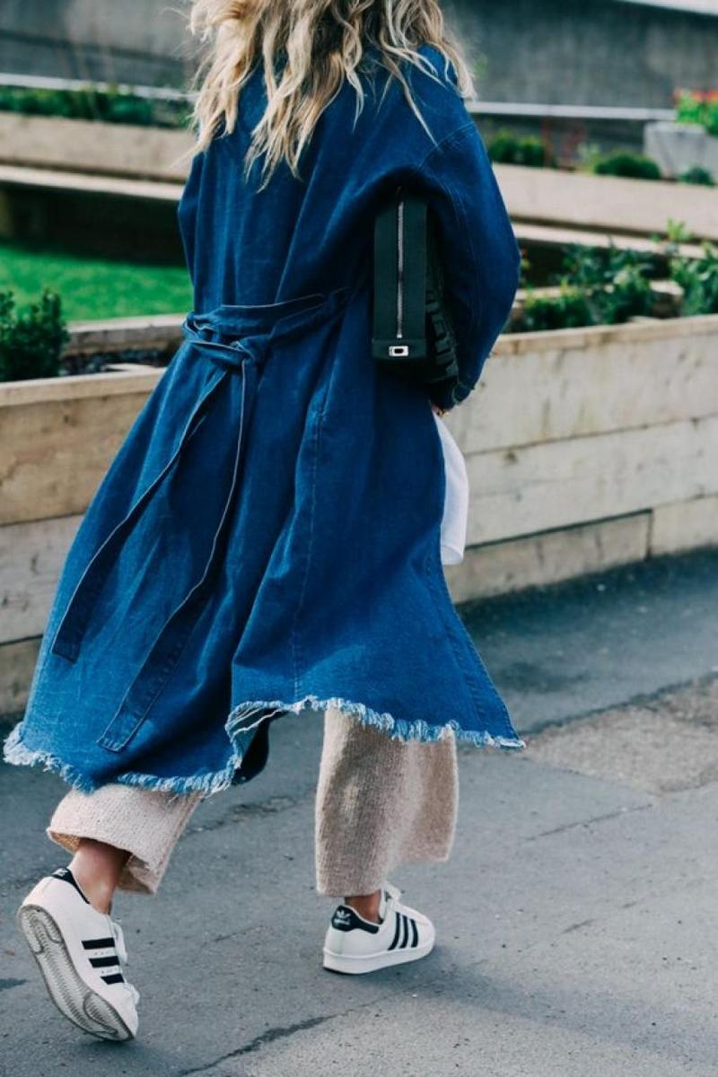 Street style photo of blogger in denim trench, knit pants and Adidas