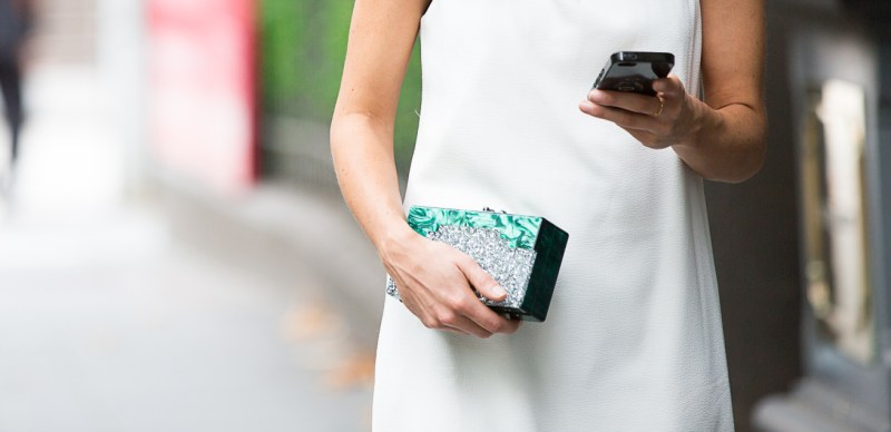 Girl wearing white dress, edie parker ombre green clutch and holding phone