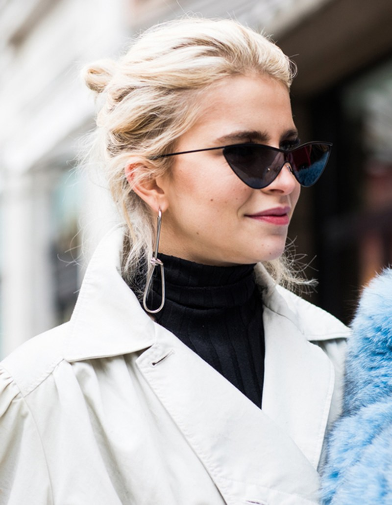 street style shot of girl wearing statement earrings, small sunglasses, black turtle neck and beige trench coat at london fashion week