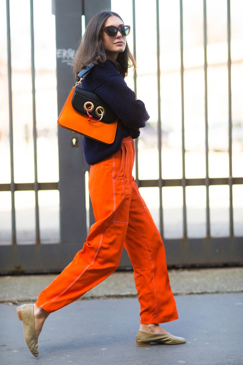 Street style shot of blogger in orange contrast stitching pants, a navy sweater and a jw anderson orange and blue bag