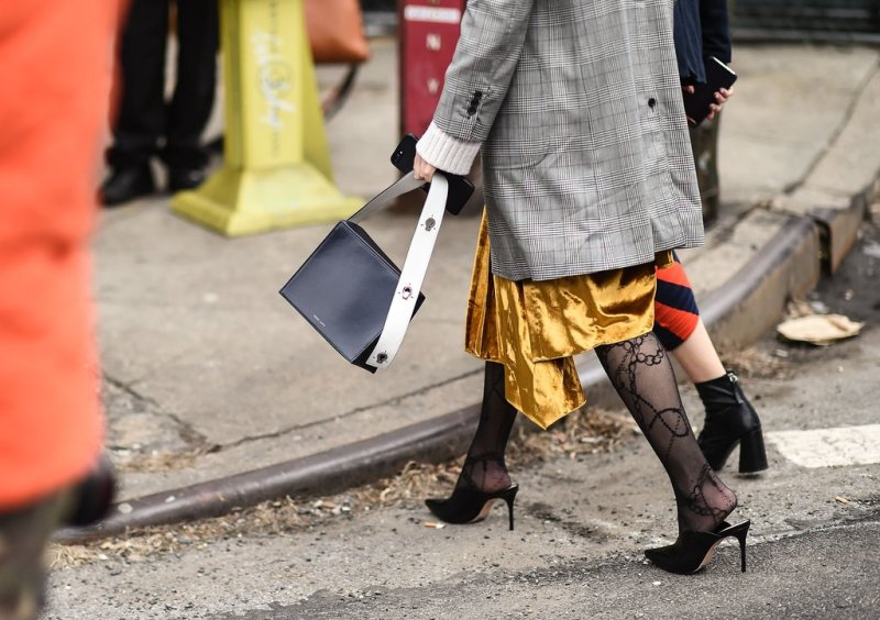 street style shot of two girls walking and carrying a danse lente bag wearing the latest spring trends