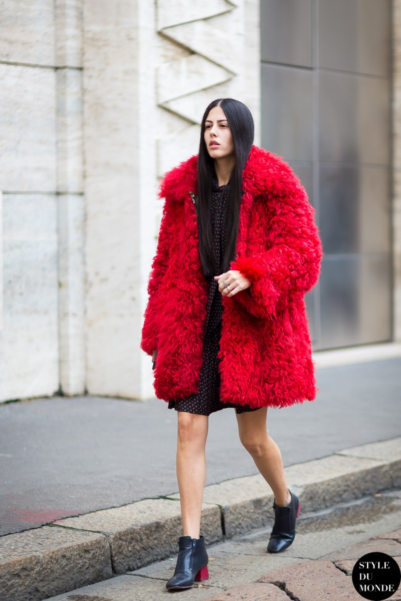 street style shot of Gilda Ambrosio in a red fur coat and black polka dot dress