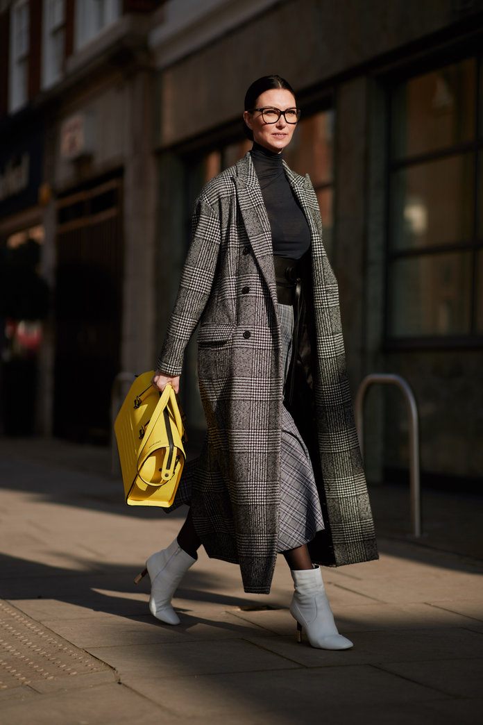 Street style shot of London fashion week in a check trench trench and jeans