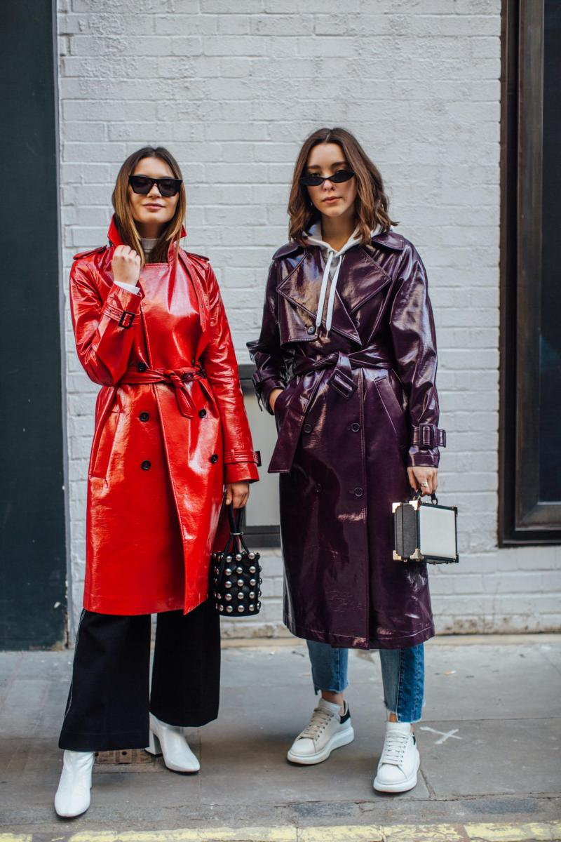Street style shot of two bloggers attending london fashion week wearing a red and purple patent leather trench coats