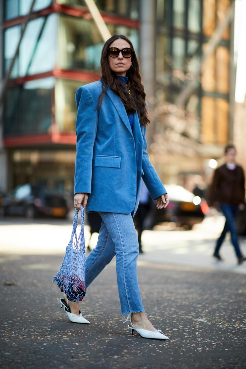Street style shot of blogger attending london fashion week wearing blue jacket, jeans, kitten heels and a net purse