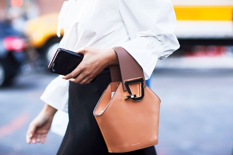 street style shot of girl holding a tan danse lente bag and a white shirt and black pants
