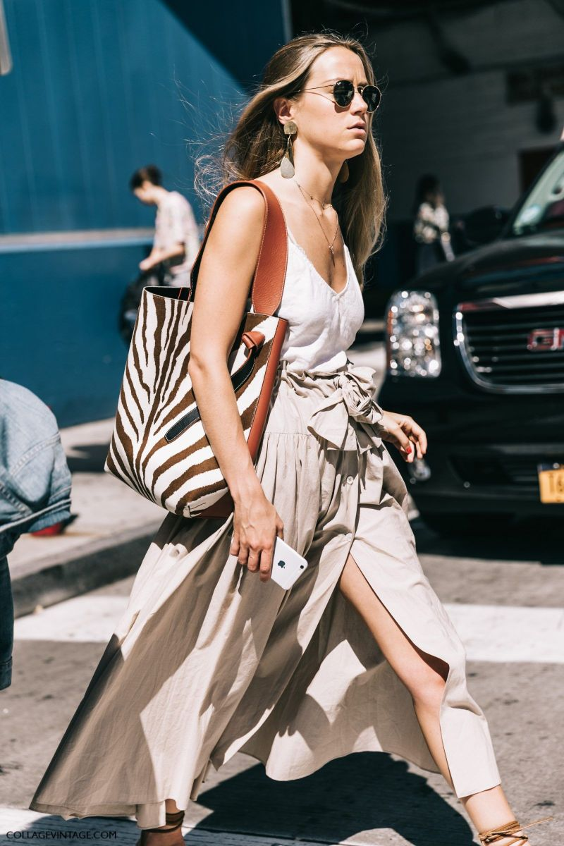 Street style shot of blogger at fashion week crossing the street wearing a nude skirt, white tank top and zebra celine tote