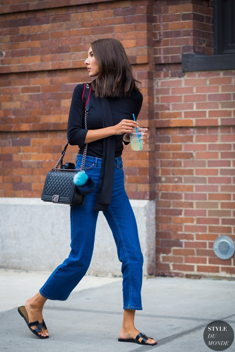 Street style shot of girl in hermes slides, blue jeans, chanel bag and a black shirt