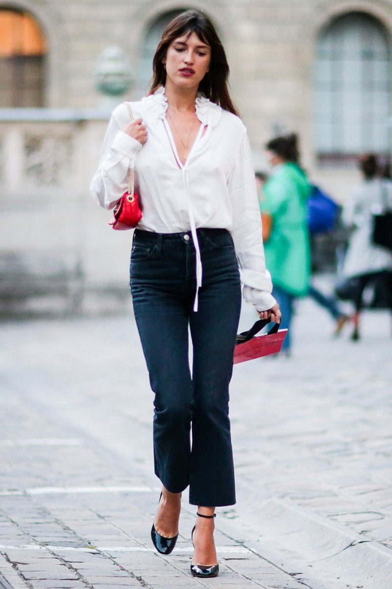 street style shot of Jeanne damas wearing a white shirt, jeans and red mini bag