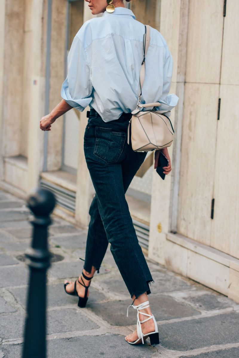 Street style shot of girl wearing strappy heels, jeans, blue shirt and loewe bag