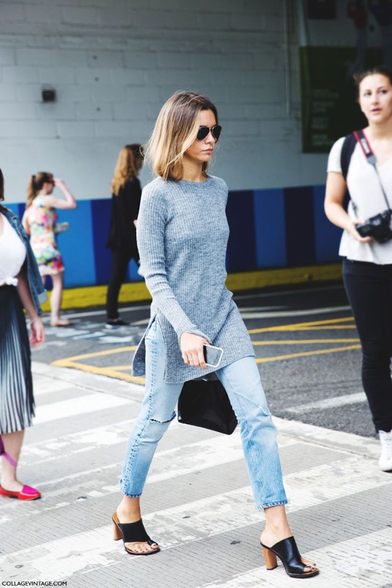Street style shot of girl wearing mules, jeans and a sweater