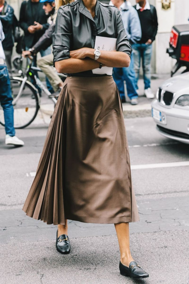 street style shot at paris fashion week of girl wearing gucci loafers, a skirt and top